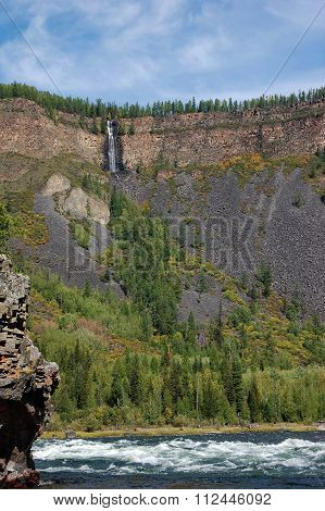 Waterfall flows down from mountain plateau into the river canyon.