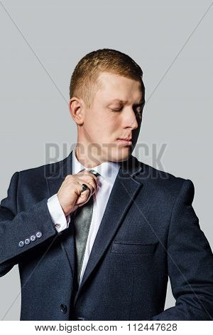 Well dressed business man adjusting his  tie.  isolated grey background