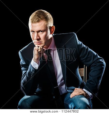 Portrait of serious elegant handsome young man in classic suit toasting with ring isolated on black