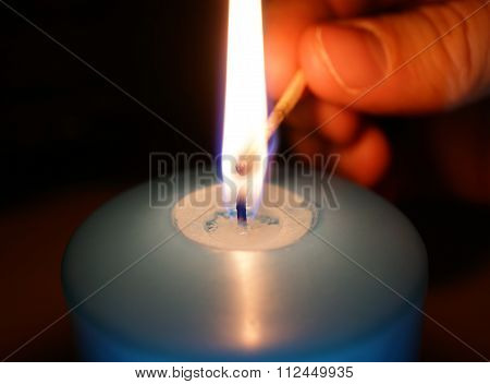 man lights a candle in dark room