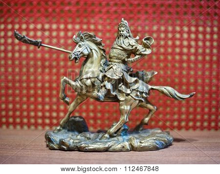 Knight on horseback miniature. Metallic knight holding a sword on the back of a horse