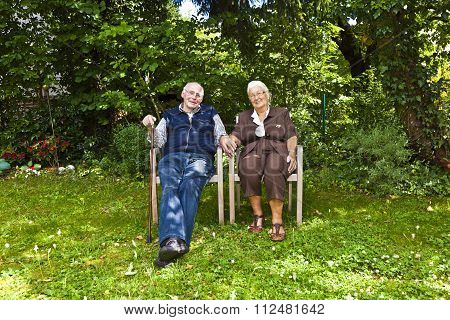 Elderly Couple Sitting Hand In Hand In Their Garden