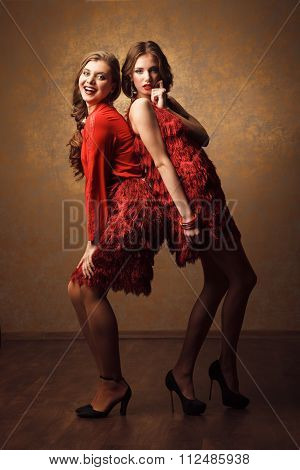 Two Beautiful Cheerful Women In Red Dress