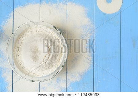 Glass Bowl With Flour On A Blue Wooden Background, Casually Sprinkled Flour