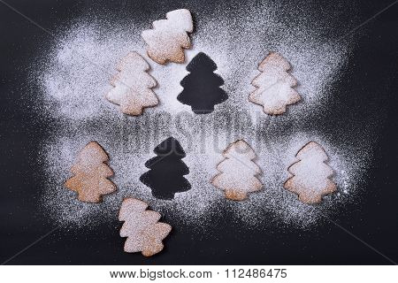 Gingerbread Cookies In Powdered Sugar On A Black Background, The Silhouette Of A Christmas Tree