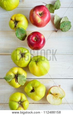 Apples And Quinces On Plank Background