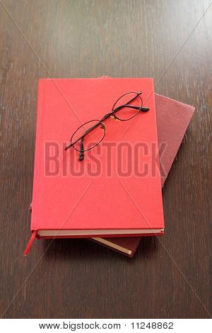 Eyeglasses and two red books