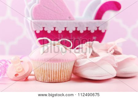 Tasty cupcakes with bow and baby shoes, decorative baby carriage on color background