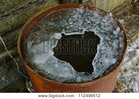 Broken ice in an old rusty barrel.