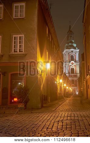 Cobbled street and church tower at night