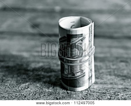 Roll of Euro banknotes on wooden background