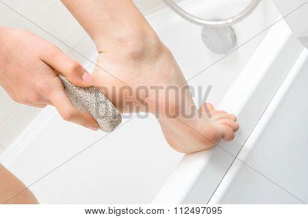 Woman scrubbing heel  use the tool for pedicure