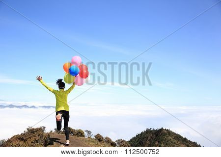 cheering young woman with colorful balloons on mountian peak