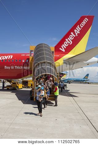 Passengers walk out on the stair from a plane of Vietjet Air