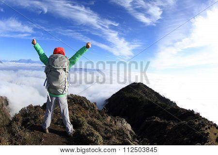 young woman hiker hiking on mountain peak