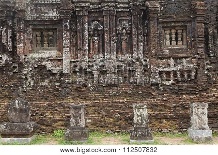 The wall of a temple with many traditonal carve details. Relief and ruin of Hindu Temples at My Son in Vietnam, an UNESCO World Heritage Site