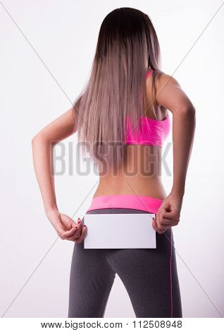 Sexy fitnes brunette in a tracksuit holding empty white board