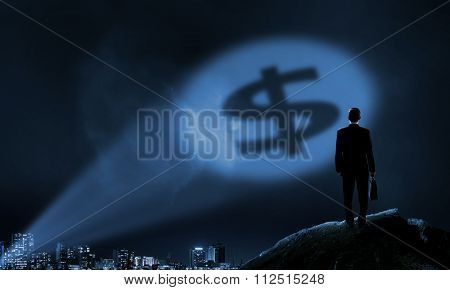 Businessman standing with back in darkness and dollar sign in spothlight