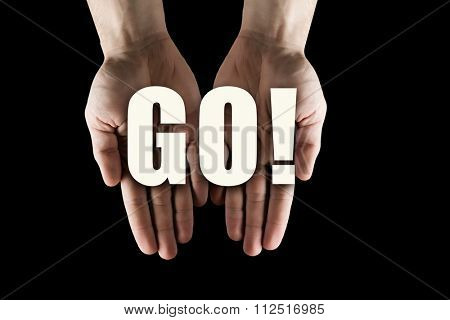 Male hands on dark background showing in palms word GO