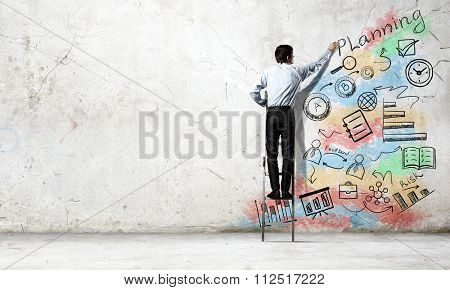 Back view of businessman standing on ladder and drawing on wall