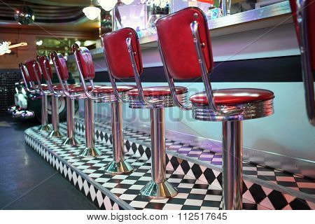 MOSCOW - JAN 21, 2015: Row of red chairs near bar counter at the American restaurant Beverly Hills Diner