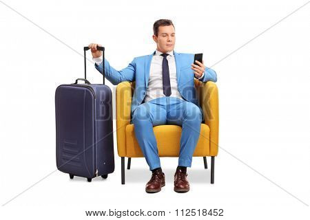 Studio shot of a young man in a fancy blue suit waiting departure with his baggage seated on an armchair and looking at his cell phone isolated on white background