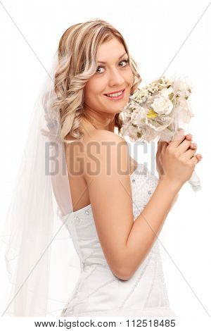 Vertical shot of a young bride in a white wedding dress holding a bouquet of wedding flowers and looking at the camera isolated on white background