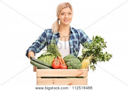 Young female farmer posing behind a crate full of fresh vegetables isolated on white background