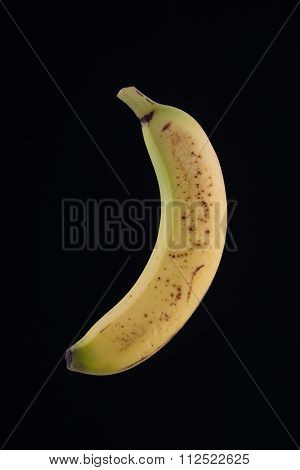 Single Organic Spotted Banana Isolated On Black
