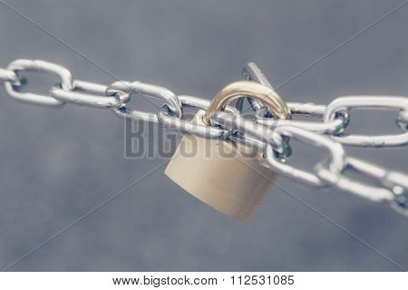 Metal key lock locked with a chain
