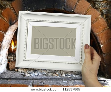 Wooden frame in beautiful woman hands. Warm Hearth on the background