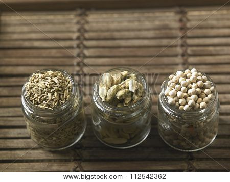 spices cumin,peppercorn and cardamon in glass containner