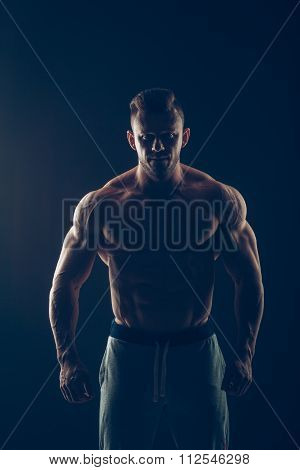 Strong Athletic Man Fitness Model Torso showing six pack abs. isolated on black background with copy