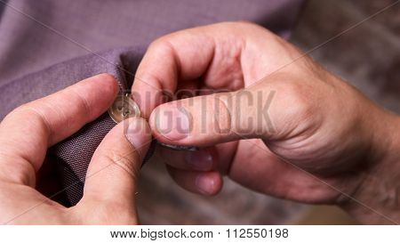 dressmaker sews a button on jacket