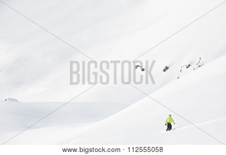 Snowboarder goes downhill in fresh powder snow in a winter mountain landscape. Italian Alps, Europe.
