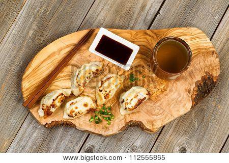 Handmade Chinese Dumplings On Fancy Wooden Server With Utensils And Green Tea