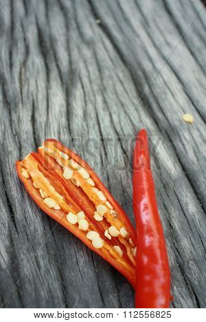 Red Chili On Background Of Brown Wood.