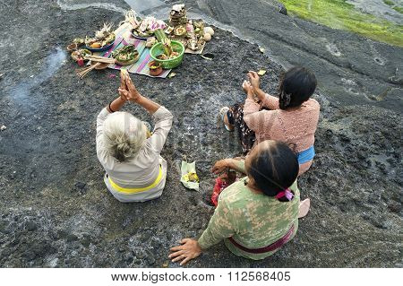 Balinese Hindu devotees pray at sunset