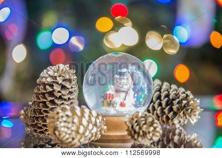 Snow Globe With Happy Snowman  On Christmas Tree Blured Background