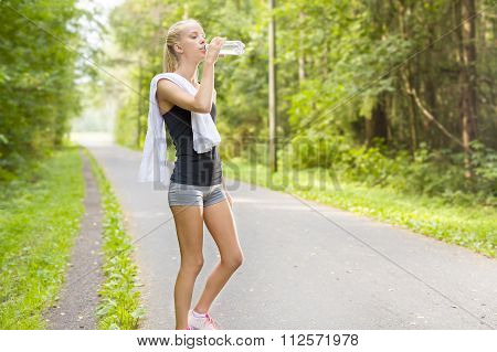 Young female runner takes a break and drinks water