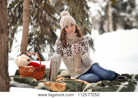 Beautiful girl sitting on a blanket in the winter in the fosest and drinking tea
