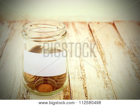 Money In The Glass On Wooden Table With Filter Effect Vintage Style