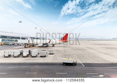 vehicles and ariplane parking in airport ramp in cloudy sky