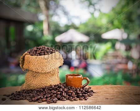 Coffee Beans In Burlap Sack On Wooden Of Blurred Coffee Shop Background