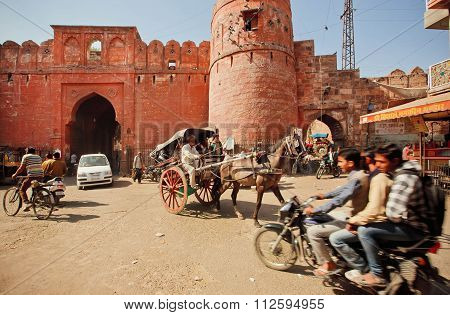 Traffic Jam On Dirt Road Of Indian City With Ancient Brick Gates