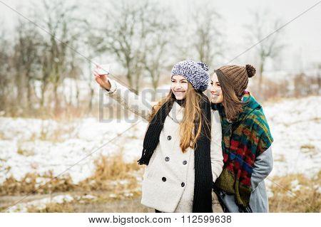 Two girlfriends taking a selfie in winter