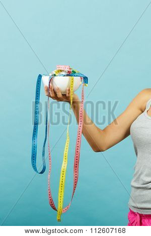 Fit Girl Holds Bowl With Many Measuring Tapes