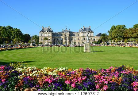 PARIS, FRANCE - SEPTEMBER 12, 2014: People enjoy sunny day in the Luxembourg Garden in Paris. Luxembourg Palace is the official residence of the French Senate.
