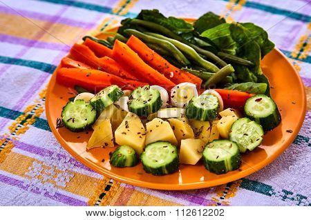 Ladle of steamed freshly harvested young vegetables including crinkle cut sliced carrots, peas and p