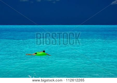 Man floating on a blue water beach
